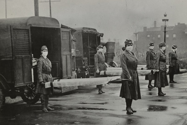 Female Red Cross ambulance attendants in St. Louis holding stretchers, awaiting influenza patients. (Library of Congress)