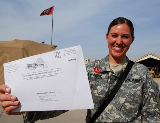 A soldier at Joint Base Balad, Iraq prepares to mail her absentee ballot this summer . (Staff Sgt. Lynette Hoke/U.S. Army)