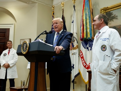 President Donald Trump, flanked by Veterans Affairs Secretary David Shulkin, right, and White House physician Ronny Jackson, speaks in the Roosevelt Room of the White House on Aug. 3, 2017, during a Veterans Affairs telehealth event. Trump fired Shulkin last month and nominated Jackson to replace him. On Wednesday, veterans groups held an event in Washington, D.C., to honor Shulkin for his work with VA. (Evan Vucci/AP)