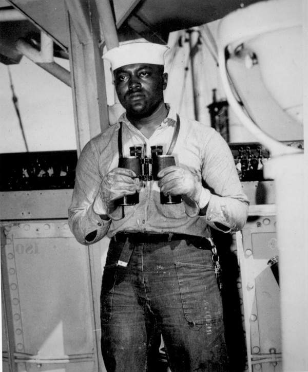 Looking to sea from the signal bridge is Napoleon Reid, Seaman 2/c., USNR, shown standing on lookout watch on a ship somewhere in the Pacific, March 19, 1945. (National Archives)
