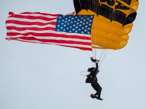 A member of the U.S. Army Golden Knights delivers the American flag at the beginning of the 2018 Power in the Pines Open House and Air Show at Joint Base McGuire-Dix-Lakehurst, N.J., in 2018. (Staff Sgt. Michael Hong/Army)