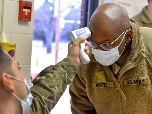 Maj. William Wratee, a U.S. Army Reserve member of the 4th Sustainment Command (Expeditionary), from Joint Base San Antonio-Fort Sam Houston, gets his temperature checked before entering the U.S. Army Reserve Center in Bismarck, N.D. (Master Sgt. Helen Miller)