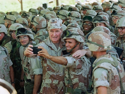 In this Jan. 1, 1993, file photo, U.S. President George H.W. Bush holds a camera, which he borrowed from the Marine to snap the picture, for a self-portrait with Marines at the airport in Baidoa, Somalia. In the final days of his presidency, George H.W. Bush committed the U.S. military to a mission many would later regret, ordering more than 20,000 troops into Somalia to