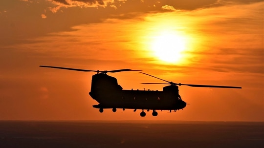 The sunset is visible behind a CH-47 Chinook helicopter as it flies near Fort Hood, Texas. (Spc. Robert Donovic/Army)