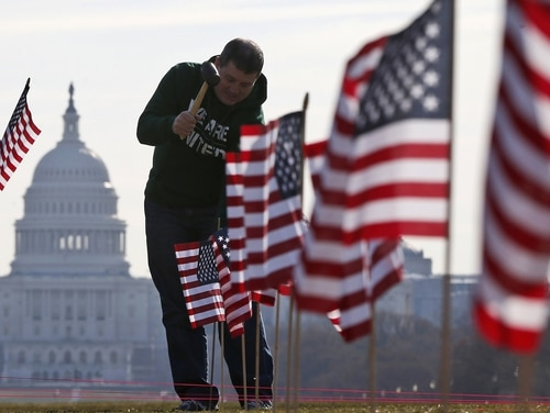 Army veteran David Dickerson of Oklahoma City, Okla., joins veterans placing flags representing veteran and service members who died by suicide on the National Mall in Washington on March 27, 2014. (Charles Dharapak/AP)