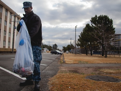 Then-Logistics Specialist 1st Class Calvin Halfacre of Fleet Air Forward in Atsugi, Japan, picks up trash along the side of the road as part of a CPO 365 base cleanup initiative in 2015. (Navy)