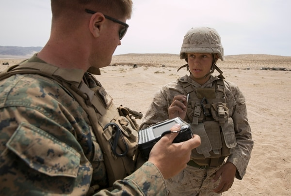 Cpl. Allison DeVries talks with Pvt. Alec Hettinger, a data recorder following an artillery assessment at Marine Corps Air Ground Combat Center Twentynine Palms in Twentynine Palms, Calif., on Friday, April 10, 2015. Participants regularly reported information to the collectors so researchers could track data throughout the assessment. (Mike Morones/Staff)