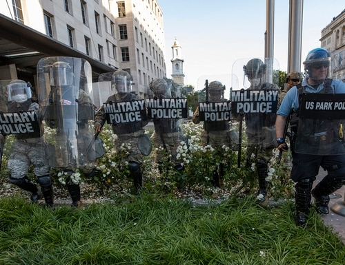 District of Columbia National Guard and U.S. Park Police advance through the white roses in front of the AFL-CIO headquarters as they move back demonstrators gathered to protest the death of George Floyd near the White House in Washington, June 1, 2020. (Alex Brandon/AP)