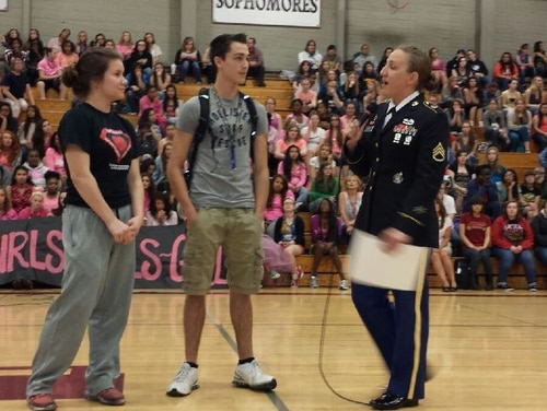 Army recruiter Staff Sgt. Molly Lewis gives recognition letters to Spencer Dean, an Army applicant, and Erica Anderson, a former Army applicant, during an assembly at Bethel High School in Spanaway Wash., May 16. (Army)