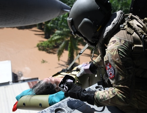 An HH-60 Black Hawk crewmember from Joint Task Force-Bravo hoists a Honduran woman in a gurney above the floodwaters of Hurricane Eta at San Pedro Sula, Honduras, Nov. 7, 2020. (Staff Sgt. Elijaih Tiggs/Air Force)