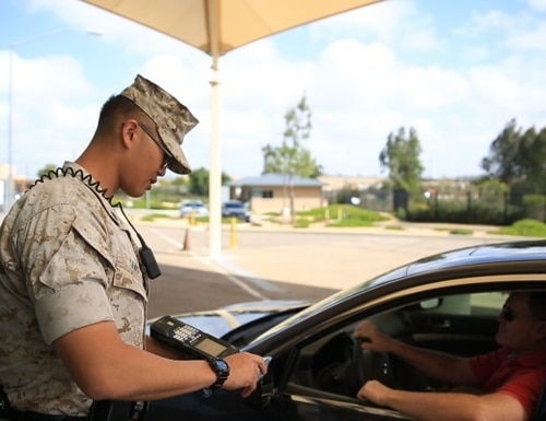 Cpl. Siheng Yang, a military police officer with the Provost Marshal's Office, checks a driver's identification before allowing him aboard Marine Corps Air Station Miramar, Calif., March 22, 2016. (Sgt. Michael Thorn/Marine Corps)