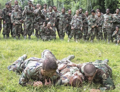 Air Force Junior Reserve Officer Training Corps cadets demonstrate how to properly drag a casualty while under enemy fire during the AFJROTC Chantilly Academy Cadet Leadership Course on Joint Base Andrews Naval Air Facility Washington, June 25, 2015. On this tactical training day portion of the course, Marine Corps recruiters in Chantilly, Virginia provided training in low crawl, high crawl, camouflage techniques, proper use of camouflage face paint, basic squad tactics and buddy carrying. (U.S. Marine Corps photo by Sgt. Anthony J. Kirby/Released)