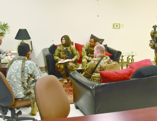 During a senior leader engagement at the Joint Readiness Training Center, in Louisiana, an Afghan role player meets with an Army adviser and a military linguist. (Army)