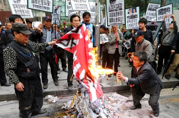 """Conservative civic organizations in 2013 burn a Japanese rising sun flag during a rally to protest Japanese lawmakers who made a visit to Yasukuni Shrine in Tokyo, in front of the Japanese embassy in Seoul, South Korea. South Korea has reiterated a demand that Japan should remove its """"rising sun"""" naval flag from a warship participating in an international fleet review in Jeju island next week. The potential display of the alleged """"war-crime flag"""" has touched a nerve in South Korea where many associate the symbol with Japanese military aggression during World War II. (Lee Jung-hoon/Yonhap via AP)"""