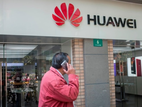 A man uses his mobile phone in front of a Huawei shop in Shanghai on May 3, 2018. U.S. officials are warning against using smartphones from Chinese cellphone maker Huawei over security concerns. (Johannes Eisele/ AFP via Getty Images)