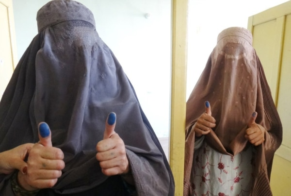 Two Afghan women hold up their blue thumbs after registering to vote in the Tarnek Wa Jaldek District on Aug. 24, 2013. (Capt. Johanna Smoke, 3rd Brigade Combat Team, 1st Infantry Division/Army)