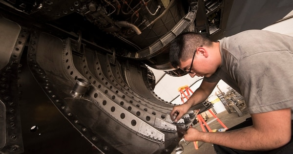 Airman 1st Class Kyle Segura, an F-15E Strike Eagle maintainer with the 332nd Expeditionary Maintenance Squadron, inspects components beneath an F-15E Strike Eagle during phase maintenance in March 2018 at an undisclosed location. The Air Force lacks a strategy for ensuring that it has enough maintainers, according to the GAO. (Staff Sgt. Joshua Kleinholz/Air Force)