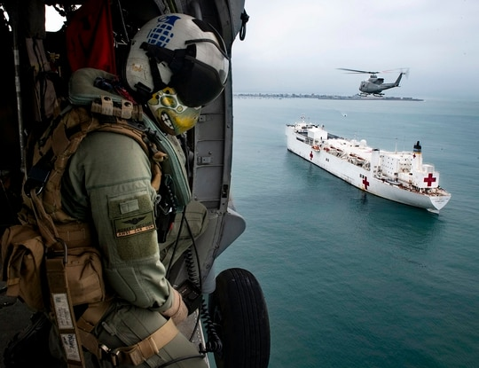 An MH-60S Sea Hawk helicopter flies over the hospital ship Comfort, which confirmed its first case of coronavirus among its staff. (MC2 Morgan K. Nall/Navy)