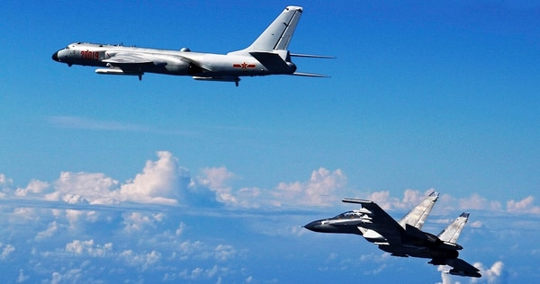A Chinese People's Liberation Army Air Force Su-30 fighter, right, flies with a H-6K bomber during a September 2016 drill near the East China Sea. While the U.S. military remains the dominant force in Asia, China is catching up quickly and is increasingly able to project power far from its shores. (Shao Jing/Xinhua via AP)