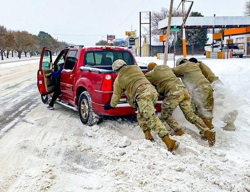 Texas Guardsmen assist a motorist stuck on snow and ice during extreme winter weather conditions in Abilene, Texas. (Capt. Martha Nigrelle/Texas Army National Guard)
