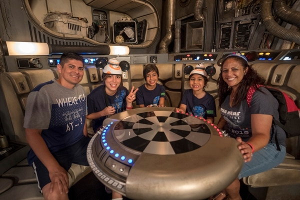 "Navy Chief Petty Officer Jorge Salas and his family sit at the chess table inside ""fastest hunk of junk in the galaxy"" as they prepare to take the controls and fly a mission aboard the most famous starship in the Star Wars galaxy."