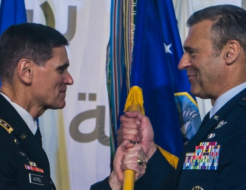 Army Gen. Joseph Votel, left, commander of U.S. Central Command, passes the guidon to Air Force Lt. Gen. Joseph T. Guastella Jr., new commander of Air Forces Central Command, during a ceremony at Al Udeid Air Base, Qatar, Aug. 30. (Senior Airman Xavier Navarro/Air Force)