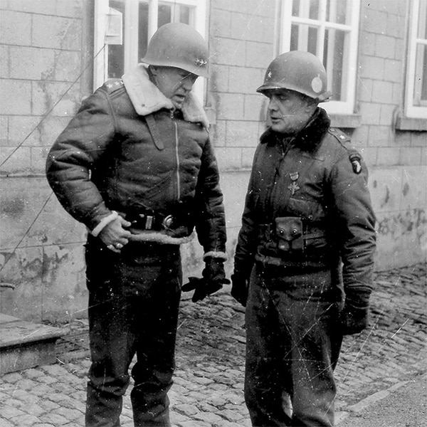 "Lt. Gen. George S. Patton speaks to Brig. Gen. Anthony McAuliffe, January 1945. Patton led the Third Army in a sweep across France and an instrumental role in defeating the German counter offensive in the Ardennes. Patton commanded the Third Army from 1944 to 1945. Third Army's unit motto ""Patton's Own – Third, Always First"" is in honor of Patton. (Army)"
