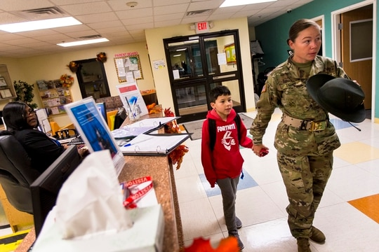 Army Sgt. Dennie Taylor signs in her son, Ethan, at the Imboden Child Development Center at Fort Jackson, S.C., on Nov. 19. (Andrew J. Whitaker/The Post And Courier via AP)