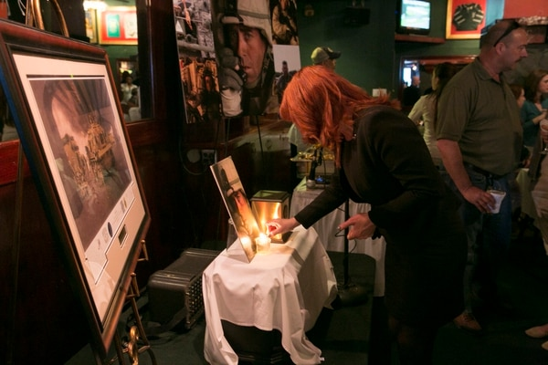 Denene Gallagher lights a candle next to the urn containing the remains of her husband retired Command Sgt. Maj. Bob Gallagher at Murphy's Grand Irish Pub in Alexandria, Va., on Sunday, April 26, 2015. Gallagher, 52, who died in October, 2014 and fought in Panama, Somalia and Iraq, will be buried at Arlington National Cemetery. (Mike Morones/Staff)