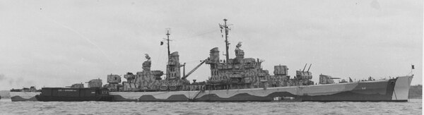 The light cruiser Juneau off New York, 1 June 1942, with an ammunition barge alongside its starboard quarter. The ship's superstructure retains its original camouflage scheme, but her hull has been repainted to a different pattern. (National Archives)