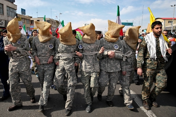 Members of Iranian Basij paramilitary force reenacted the January capture of U.S sailors by the Revolutionary Guard in the Persian Gulf, in a rally commemorating the 37th anniversary of Islamic Revolution in Tehran on Feb. 11, 2016. The nationwide rallies commemorated Feb. 11, 1979, when followers of Ayatollah Khomeini ousted U.S.-backed Shah Mohammad Reza Pahlavi. (Ebrahim Noroozi/AP)