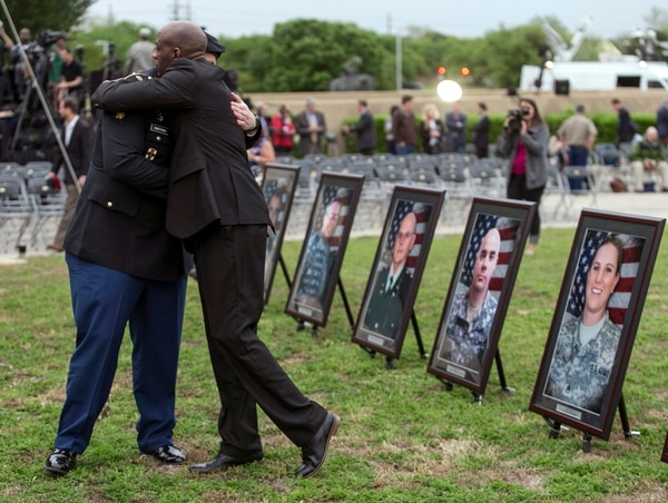 Purple Heart recipients Pfc. James Armstrong, left, and Chief Warrant Officer 2 Christopher Royal hug as they look at pictures of co-workers who were killed in the 2009 Fort Hood shooting, prior to a ceremony, Friday, April 10, 2015, at Fort Hood, Texas. Survivors and family members of those killed during the attack were awarded medals: a Purple Heart for military personnel and Defense of Freedom Medals for civilians. (AP Photo/Austin American-Statesman, Rodolfo Gonzalez, Pool)