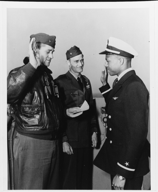 Ensign Jesse L. Brown takes the oath of office on board the aircraft carrier Leyte (CV-32), 26 April 1949. Administering the oath is the ship's commanding officer, Capt. William L. Erdmann. Lt. Cmdr. E.D. Williams (center) is witnessing the ceremony. (National Archives)