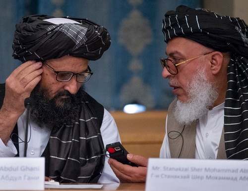 In this May 28, 2019, file photo, Mullah Abdul Ghani Baradar, the Taliban group's top political leader, left, and Sher Mohammad Abbas Stanikzai, the Taliban's chief negotiator, talk to each other during a meeting in Moscow, Russia. (Alexander Zemlianichenko/AP)