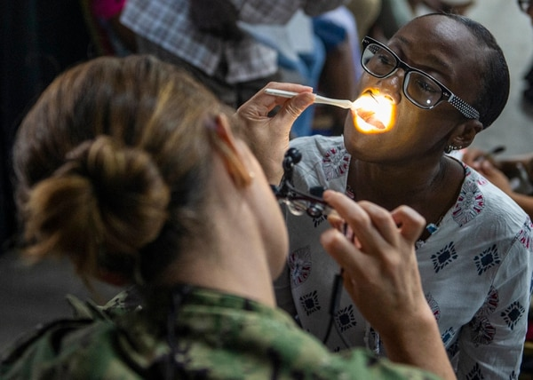 Lt. Cmdr. Julie Suguitan, a dentist assigned to the hospital ship Comfort, examines a Saint Lucian woman's teeth at a temporary medical treatment site in Castries, Saint Lucia, on Sept. 26. (Mass Communication Specialist 3rd Class Brendan Fitzgerald/Navy)