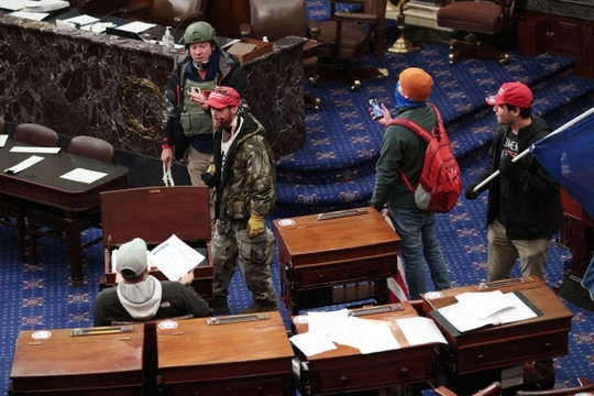 Protesters enter the Senate Chamber on Jan. 06, 2021, in Washington, D.C. The man wearing military body protection and helmet was later identified as Larry Rendall Brock Jr., an Air Force veteran. (Win McNamee/Getty Images)