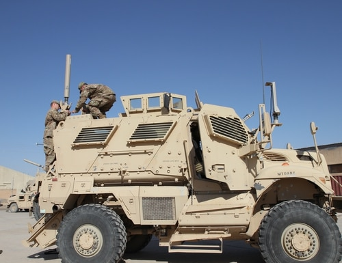 Army Reservists install a Blue Force Tracker system on a tactical vehicle for the 300th Sustainment Brigade Det. 2 in Iraq in 2016. (Spc. Milagro Perez/Army)