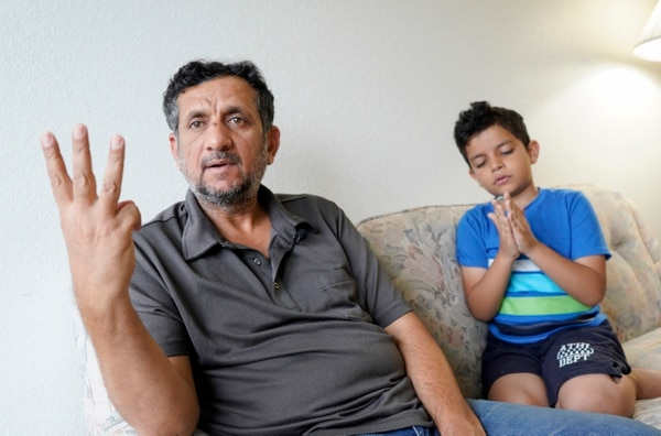 In this Sept. 29, 2018, photo, Hadi Mohammed gestures as he sits with his 9 year old son Mohammed Ghaleb, in their Lincoln, Neb., apartment. Death threats drove Hadi Mohammed out of Iraq and to a small apartment in Nebraska, where he and his two young sons managed to settle as refugees. But the danger hasn't been enough to allow his wife to join them. (Nati Harnik/AP)