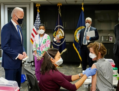President Joe Biden, standing left, visits a COVID-19 vaccination site and watches as Dr. Navjit Goraya gives a vaccine to Air Force Col. Margaret Cope at the VA Medical Center in Washington, D.C. on March 8. Others at the event included (from left) Pharmacist Deepika Duggineni, White House COVID-19 Response Coordinator Jeff Zients and Veterans Affairs Secretary Denis McDonough. (Patrick Semansky/AP)