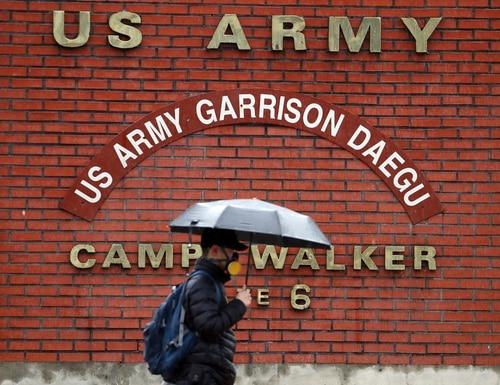 In this Tuesday, Feb. 25, 2020, photo, a man passes by U.S. Army base Camp Walker, in Daegu, South Korea. (Kim Hyun-tae/Yonhap via AP)