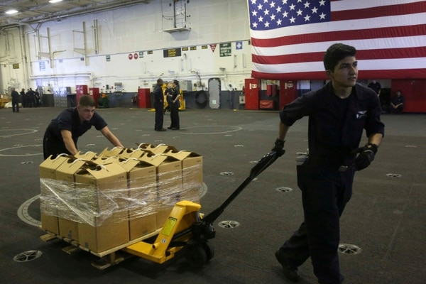 Sailors aboard the aircraft carrier Abraham Lincoln move pallets of water in preparation to support those affected by Hurricane Irma. (Aviation Boatswain's Mate 2nd Class Lauren D. Smith/ Navy)