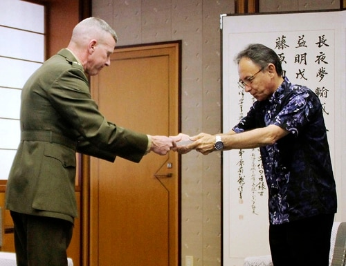 Okinawa Gov. Denny Tamaki, right, hands a letter of protest to Lt. Gen. Eric Smith, U.S. Marine Corps commander in Japan, at Okinawa Prefectural Government Office in Naha, Okinawa, Japan, Monday, April 15. (Kyodo News via AP)