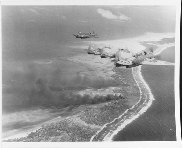 Two TBF-1 Avenger bombers from the aircraft carrier Coral Sea fly over Butaritari Island, Makin Atoll, during the pre-invasion, 20 November 1943. The Western tank trap and on Chong's wharf are in the lower center. Fires are burning in the area of King's wharf, and a wrecked Japanese H8K (