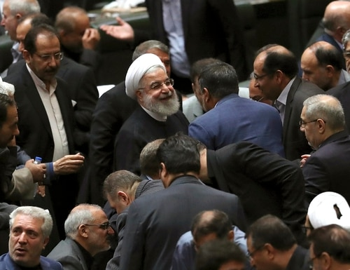 Iranian President Hassan Rouhani, center, listens to a lawmaker after defending his proposed tourism and education ministers, in Tehran, Iran, Tuesday, Sept. 3, 2019. (Vahid Salemi/AP)