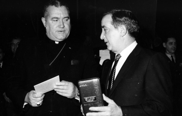 Bishop William J. Moran, D.D., Auxiliary Bishop, Military Ordinariate, chats with Mr. James S. Capodanno of Staten Island, New York, who holds the Medal of Honor awarded posthumously to his brother, Lt. Vincent R. Capodanno, a Navy Chaplain. The Medal was presented to Mr. Cappodanno by Secretary of the Navy Paul R. Ignatius in a ceremony held at the Washington Navy Yard, Washington DC, on Tuesday, January 7, 1969. (Naval History & Heritage Command)