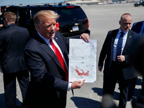 In this March 22, 2019, photo, President Donald Trump holds a copy of two maps of Syria as he arrives on Air Force One, Friday, March 22, 2019, at Palm Beach International Airport, in West Palm Beach, Fla. (Carolyn Kaster/AP)