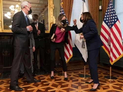 Vice President Kamala Harris (right,) bumps elbows with Kari McDonough, after ceremonially swearing in McDonough's husband, Denis (far left) as the Veterans Affairs Secretary on Feb. 9, 2021, at the Eisenhower Executive Office Building on the White House complex in Washington, D.C. Behind them are McDonough's sons. (Jacquelyn Martin/AP)