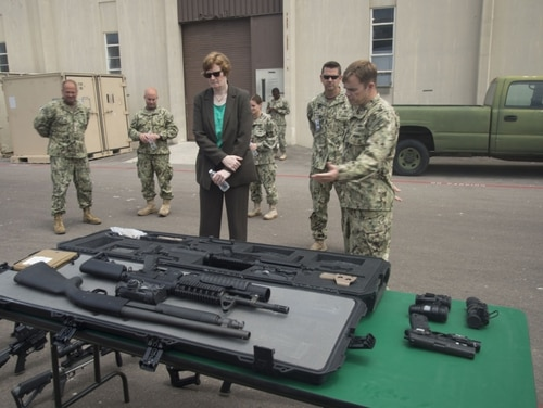 Chief Gunner's Mate Grover White, right, shows off different weapons to Nancy Harned, executive director of Navy Expeditionary Combat Command, in 2015. White pleaded guilty last month for failing to keep track of gear. (Navy)