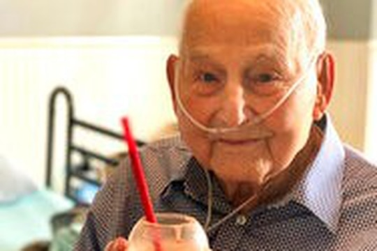World War II veteran and COVID-19 survivor Major Wooten holds a celebratory milkshake on his 104th birthday on Thursday, Dec. 3, 2020, in Madison, Alabama. (Holly Wooten McDonald via AP)