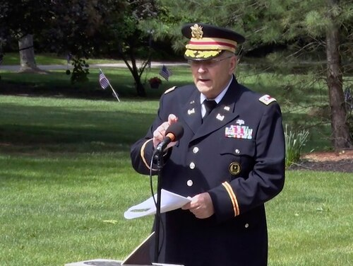 In this frame grab from video provided by Hudson Community Television, retired Army Lt. Col. Barnard Kemter taps the microphone after organizers turned off the audio during his speech at a Memorial Day ceremony on May 31, 2021, in Hudson, Ohio. (Hudson Community Television via AP)